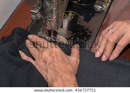 Tailor using industrial sewing machine  - stock photo