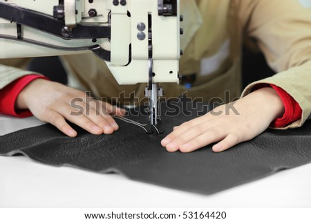 Tailor working on a sewing machine at textile factory - stock photo