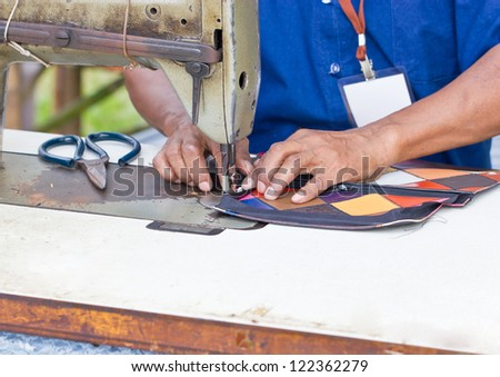 Tailor working on a vintage sewing machine. - stock photo