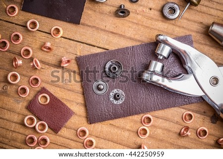 Tailor workplace with pieces of leather and rivets - stock photo