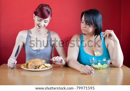 Tailored diet. Skinny woman is happy because she can eat huge meals, while the overweight woman is looking sadly at her because she has to eat just a few leaves of lettuce. Selective focus. - stock photo