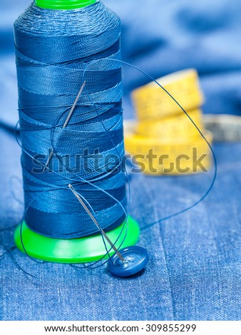 tailoring still life - thread bobbin with needles, button, measure tape on blue silk textile - stock photo