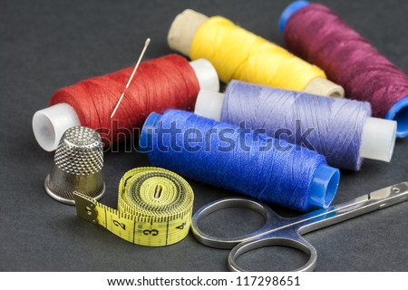 Tailors tools - scissors, spools of thread, measure, needle and thimble - isolated on black background - stock photo