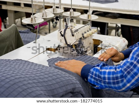 Tailors working in the sewing workshop using tailoring machine - stock photo