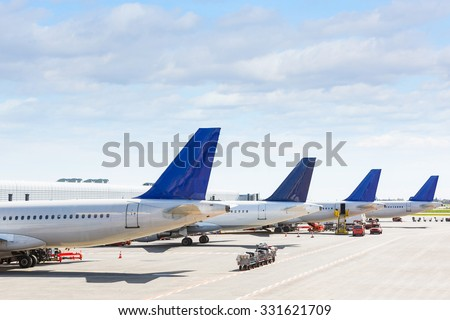 Tails of some airplanes at airport during boarding operations. They are four planes on a sunny day, with a blue sky. Travel and transportation concepts. - stock photo