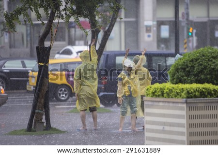 TAIPEI, TAIWAN - JUN 10: Falun Gong devotees protest the Chinese government's alleged persecution of their movement under the rainstorm in Taipei, Taiwan on June 10 2015. - stock photo
