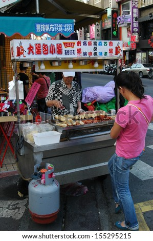 TAIPEI, TAIWAN-JUNE 14: Customer buys street food from street vendor on June 14, 2013 in Taipei, Taiwan. There are over 100 night markets scattered throughout the city.  - stock photo