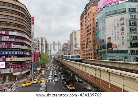 TAIPEI, TAIWAN - MAY 5: View of the intersection Zhongxiao Fuxing Metro station with trains and traffic passing through on May 5, 2016 in Taipei, Taiwan