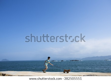 Taipei,Taiwan-Oct 27,2015:Asian boy chasing a  dog on the seaside close to Taipei city - stock photo