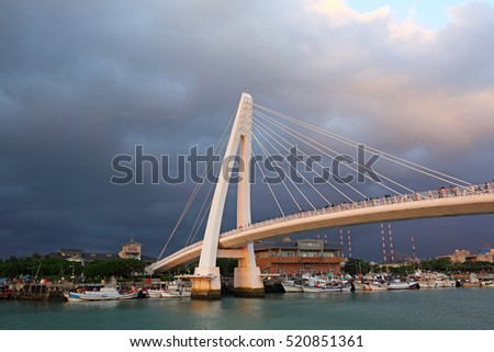 TAIPEI, TAIWAN - OCT 31: Sunset view of tourists and taiwanese walking and visit Fisherman's Wharf from Lover's Bridge on October 31, 2016. Tamsui is popular as a site for viewing sunset.