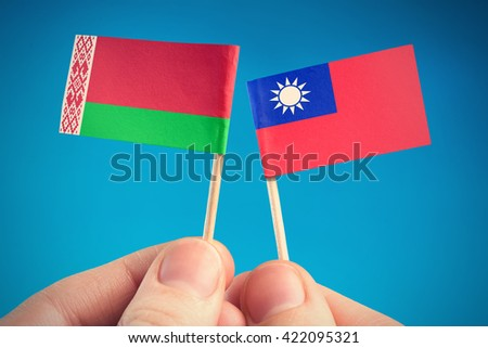 Taiwan and Belarus - flags in the hands on blue background - stock photo