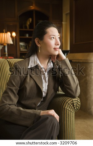 Taiwanese mid adult buisinesswoman looking to side with head resting on hand. - stock photo