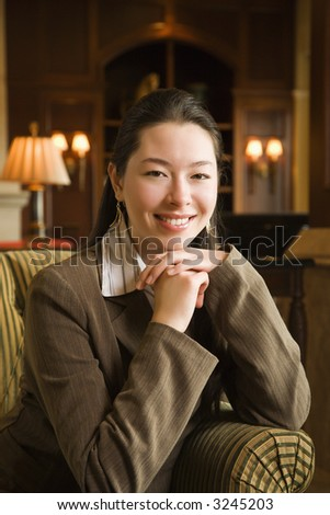 Taiwanese mid adult buisinesswoman smiling at viewer with chin resting on hands. - stock photo