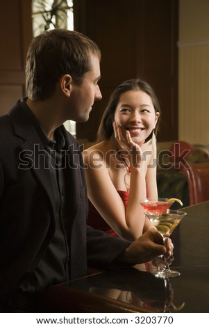 Taiwanese mid adult woman and Caucasian man standing at bar with drinks. - stock photo