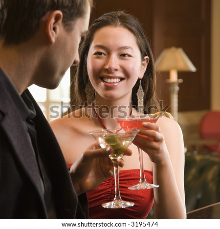 Taiwanese mid adult woman and Caucasian man toasting martinis.