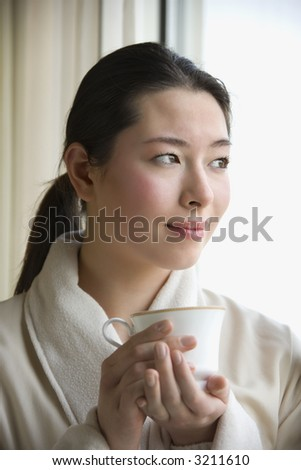 Taiwanese mid adult woman in bathrobe drinking coffee and looking out window. - stock photo