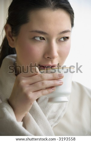 Taiwanese mid adult woman in bathrobe drinking coffee and looking to side. - stock photo