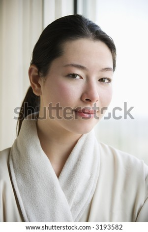 Taiwanese mid adult woman in bathrobe looking at viewer. - stock photo