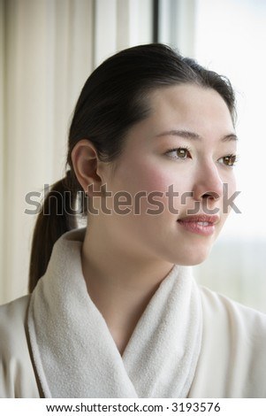 Taiwanese mid adult woman in bathrobe looking out window. - stock photo