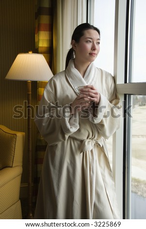 Taiwanese mid adult woman in bathrobe looking out window holding coffee cup. - stock photo