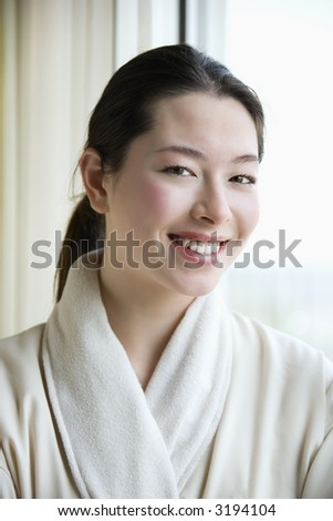 Taiwanese mid adult woman in bathrobe smiling at viewer. - stock photo