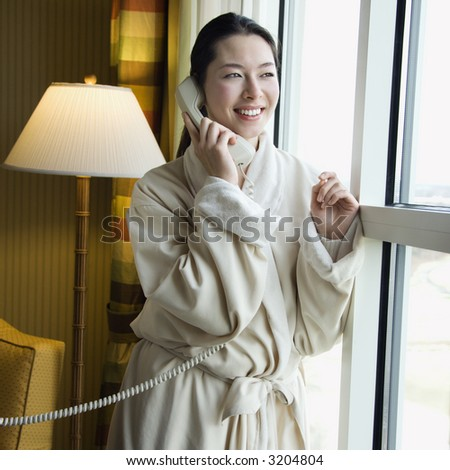 Taiwanese mid adult woman in bathrobe talking on phone and looking out window. - stock photo