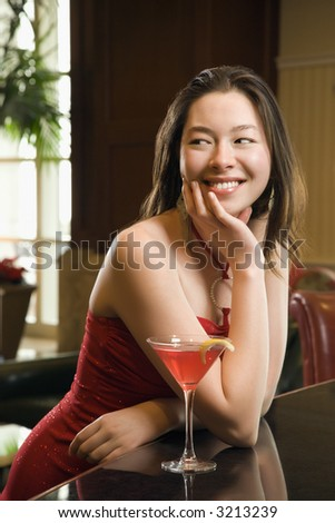 Taiwanese mid adult woman in red dress smiling and standing at bar with drink. - stock photo