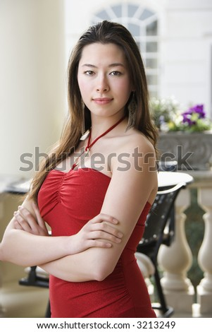Taiwanese mid adult woman in red dress with arms crossed looking at viewer. - stock photo