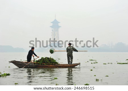 TAIZHOU, CHINA - NOVEMBER 21, 2014: Unidentified Chinese women scoop water hyacinth (a weed) from the waters of the Qinhu National Wetland Park outside of Taizhou China. - stock photo