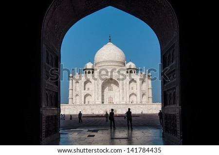 Taj Mahal in India in backlight seen from the arch of the mosque - stock photo