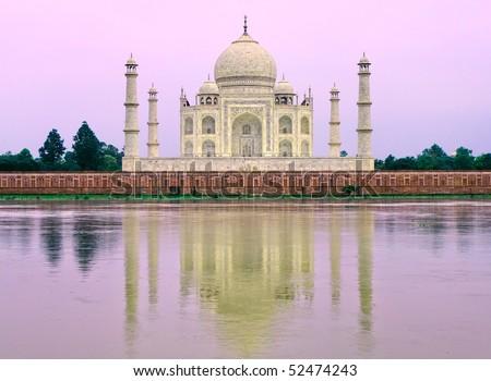 Taj Mahal in yellow light on pink sunrise - stock photo