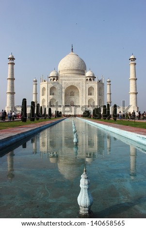 Taj Mahal monument with reflection in water in Agra, India. Taj Mahal is considered one of the seven wonders of world and is a UNESCO world heritage site.  - stock photo