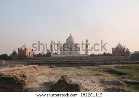 Taj Mahal, the white marble mausoleum with four minarets and two red sandstone buildings on either side of the mausoleum can be seen from across the Yamuna river during sunset close up  - stock photo