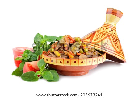 Tajine, moroccan national dish full of meat and vegetables with marjoram and tomatoes on a white background - stock photo