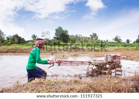 TAK, THAILAND - 20 AUGUST 2013: Thai farmer using walking tractors for cultivated soil for rice plantation at tak province, north of Thailand.
