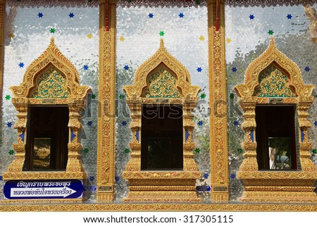 TAK, THAILAND - NOVEMBER 20, 20103: Exterior of the Wat Mani Phraison temple in Mae Sot, Thailand. Outside walls of the temple are covered with thousands of small pieces of glass.