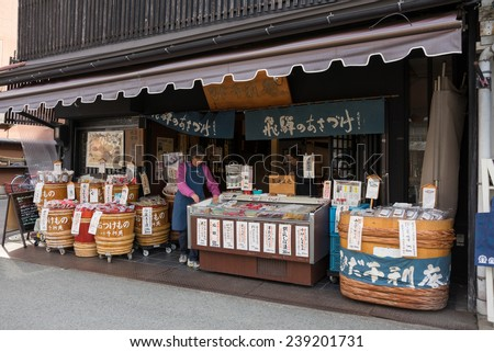 TAKAYAMA, JAPAN - DECEMBER 3, 2014: Vendors at their shop at the Miyagawa morning market in Takayama, Japan. This marketplace sells food items, groceries to farm produce and is common in rural Japan. - stock photo