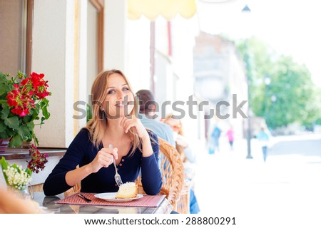 Take a break! Attractive young woman eating cake at street cafe. - stock photo