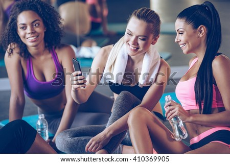 Take a look at my workout plan! Beautiful young women in sportswear discussing something with smile and using smartphone while sitting on exercise mat at gym