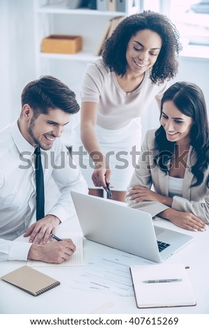Take a look at this chart! Top view of young beautiful African woman pointing at laptop with smile while standing at office with her coworkers