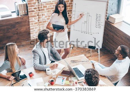 Take a look at this numbers! Top view of beautiful young woman standing near whiteboard and pointing on the chart while her coworkers looking at her and sitting at the table in office - stock photo
