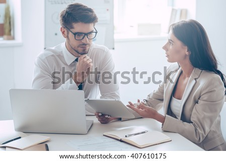 Take a look here! Young beautiful woman discussing something and showing her digital tablet to her coworker while sitting at the office table - stock photo