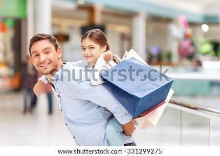 Take a ride. Pleasant joyful agreeable father holding his daughter on the back and having fun while making shopping - stock photo