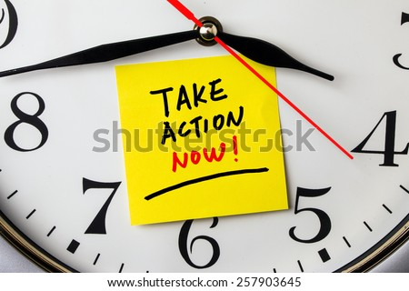 take action now on post-it stuck to a wall clock - stock photo