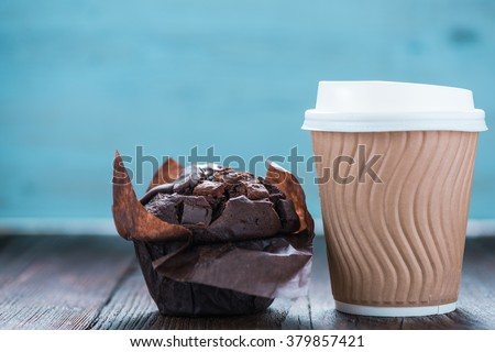Take away coffe and chocolate muffin on wooden background with copy space for text or advert - stock photo