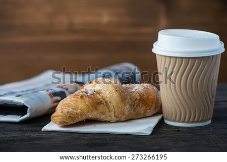 Take away coffee and fresh croissant and newspaper on wooden background - stock photo