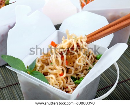 Take away egg noodles on chopsticks in a take away container. - stock photo