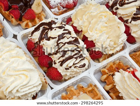 Take away street waffles topped with strawberries, chocolates and whipped cream in Brussels of Belgium. - stock photo