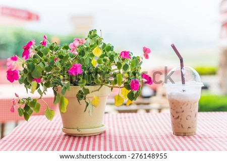 take-home cup of ice coffee on table. - stock photo