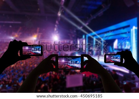 Take photo crowd in front of concert stage blurred